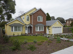 Lakeburn - New American style with a recessed front porch, arched colonial windows bay windows a mixture of materials in the façade built by Farm Houses of Australia